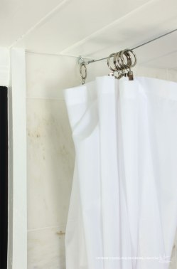 Use cable and clips for a low profile shower curtain: https://ourhumbleabodeblog.com/2014/01/06/minor-tweaks-big-impact/